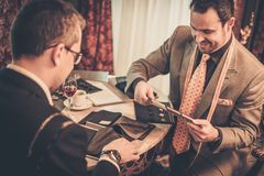 Tailor and client choosing materials for suit Royalty Free Stock Photo