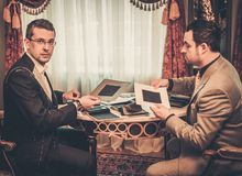 Tailor and client choosing materials for suit Stock Photography