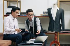 Tailor and client. Professional tailor and client discussing model on jacket Stock Photo