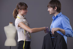 Tailor and customer. Handshake between tailor and customer with business jacket Royalty Free Stock Photo