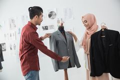 Tailor and customer talking about the suit. Portrait of muslim tailor and customer talking about the suit in the office Stock Photo