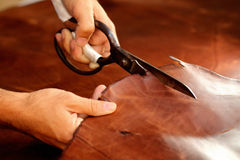 Tailor cutting animal skins, leather at textile factory Royalty Free Stock Photos