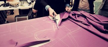 Tailor cutting fabric for bespoke suit.  Stock Photo
