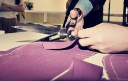 Tailor cutting fabric for bespoke suit.  stock images