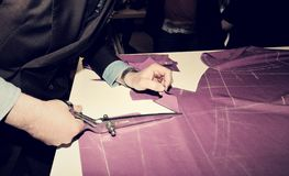 Tailor cutting fabric for bespoke suit.  Royalty Free Stock Photos