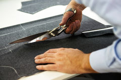 Tailor cutting fabric with large scissors Stock Images