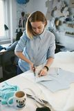 Tailor Cutting Fabric With Scissors In Atelier. Portrait Of Woman Making Clothes For Dogs, Cutting Textile On Table stock photography
