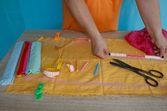 Tailor cutting fabric using large scissors or shears as he follows the chalk markings of the pattern, close up of his hands Stock Image