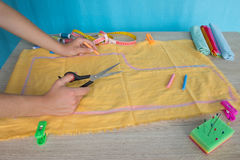 Tailor cutting fabric using large scissors or shears as he follows the chalk markings of the pattern, close up of his hands Royalty Free Stock Photography