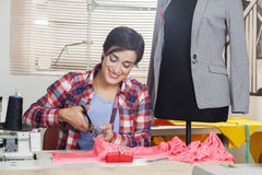 Tailor Cutting Fabric At Workbench By Mannequin Royalty Free Stock Image