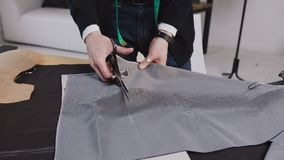 A tailor cutting a high quality fabric gray, before you sew it and make a piece of high fashion clothing. The tailor or. Fashion designer uses professional stock video