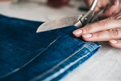Tailor cutting jeans with scissors. At workshop stock photo