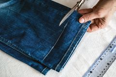 Tailor cutting jeans with scissors. At workshop stock photography