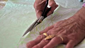 Tailor cutting material with scissors Royalty Free Stock Photography