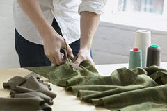 Tailor Cutting Piece Of Cloth At Table In Fashion Studio. Midsection of young male tailor cutting piece of cloth at table in fashion studio Stock Photography