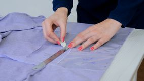 Tailor, designer drawing line on fabric at sewing studio stock photography