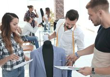 Tailor and designers to discuss men`s suit royalty free stock photos