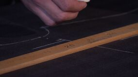 A tailor is drawing lines on a fabric with his chalk in order to make a suit, he is making some alterations