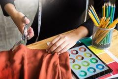 Tailor& x27 för handhackskräddare; s scissors torkduken som klipper ett stycke av fa Arkivfoto