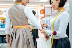 Tailor fitting a bespoke dress to a woman customer. Tailor fitting a bespoke dress to a women customer with measure tape around her neck royalty free stock photos