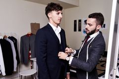 Tailor Fitting  Model for Bespoke Suit. Portrait of handsome young tailor fitting bespoke suit to model  in traditional atelier studio Royalty Free Stock Images