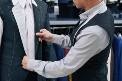 Tailor fitting suit. Cropped image of tailor fitting bespoke suit to client in atelier royalty free stock image