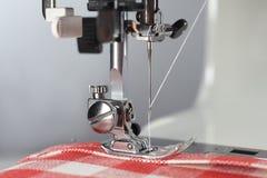 tailor Funktionsduglig del för symaskin med linnetyg i den röda cellen arkivfoton
