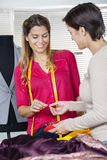 Tailor Giving Pin To Colleague In Factory Stock Photo