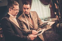 Tailor and his client. Tailor and client choosing cloth and buttons for custom made suit Stock Photos