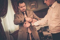 Tailor and his client. Tailor measuring client for custom made suit tailoring Stock Photo