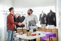 Tailor with his customer talking Royalty Free Stock Photos