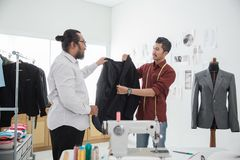 Tailor with his customer talking. About the suit in the workshop Stock Image