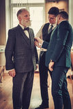 Tailor and his protege measuring client for custom made garment Royalty Free Stock Photography