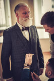 Tailor and his protege measuring client for custom made garment Royalty Free Stock Photo