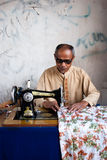 Tailor in Indonesia. ENDE, INDONESIA - AUGUST 5: a man sewing on the street near the ikat market of Ende on August 5th 2010 Royalty Free Stock Photography
