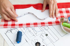 A tailor is laying out a dress/Sewing layout Stock Photos