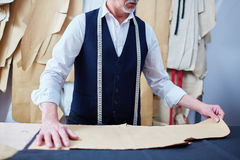 Tailor Making Bespoke Clothes in Atelier. Portrait of experienced old tailor working with patterns in atelier shop stock photography
