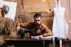 Tailor man sews clothes. Handsome man tailor or dressmaker with beard and moustache sews clothes on vintage sewing machine in rustic workshop Stock Photo