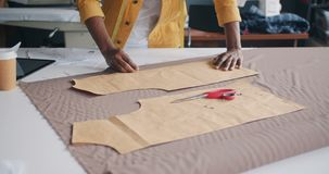 Tailor manufacturing handmade clothing outlining model on material. Male tailor manufacturing handmade clothing outlining model on material working in workshop stock footage