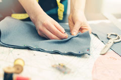Tailor marking the fabric with sewing pins stock photography