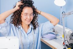 Tailor massaging wavy hair while working at tailor shop. Tailor massaging wavy while working at tailor shop. meditation. positive thoughts Royalty Free Stock Images