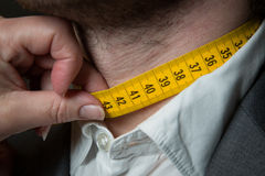 Tailor measuring. The size for a tailor made suite for a male model Royalty Free Stock Photo