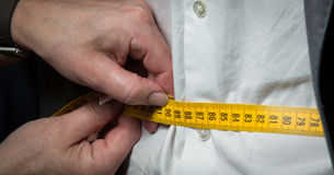 Tailor measuring. The size for a tailor made suite for a male model Royalty Free Stock Photography