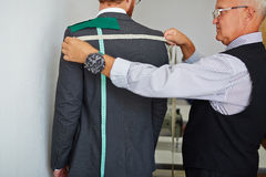 Tailor Measuring Back of Client to Make Suit Royalty Free Stock Images
