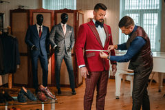 Tailor measuring client for custom made suit tailoring. Tailor measuring client for custom made suit tailoring Royalty Free Stock Photo