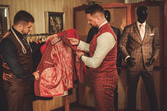 Tailor measuring client for custom made suit tailoring. Tailor measuring client for custom made suit tailoring Royalty Free Stock Photography