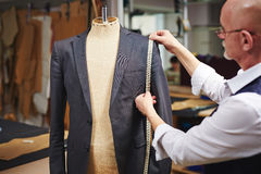 Tailor Measuring Custom Suit in Atelier. Portrait of mature tailor measuring jacket with tape fitting custom suit on mannequin Royalty Free Stock Photos