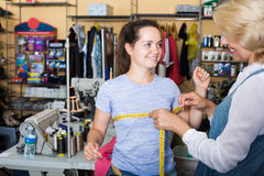 Tailor measuring customer in atelier Royalty Free Stock Photo