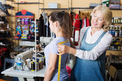 Tailor measuring customer in atelier. Professional mature tailor measuring customer in sewing atelier Royalty Free Stock Image