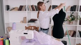Pretty woman tailor is measuring a dress form with a tape